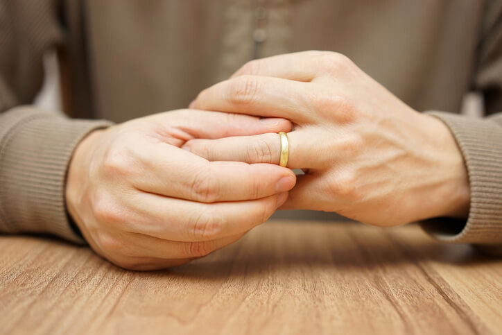 Picture of man taking off his wedding ring symbolising divorce