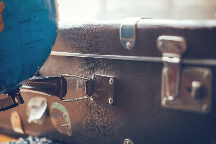 globe next to the packed suitcase of a person who has sold their home to move abroad