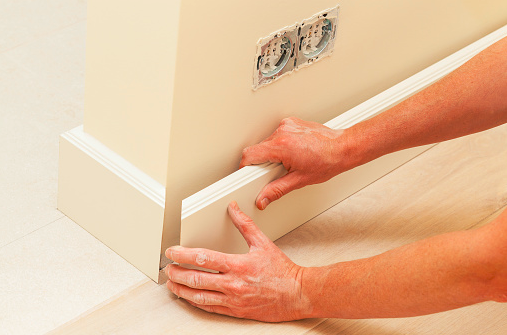 Person adding in plastic skirting boards which help absorb flood water more than wooden skirting boards